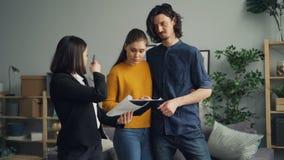 Compradores da menina e do indivíduo que falam ao contrato da leitura do agente de abrigo no apartamento novo