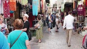 Compradores en la calle estrecha en Jerusalén vieja, Israel