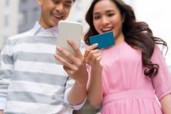 Compradores que compran en línea con la tarjeta de crédito y el teléfono elegante que se colocan al lado de un escaparate en la c imagen de archivo libre de regalías