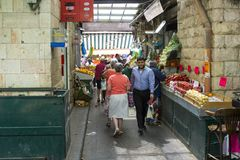 Compradores que pasan a través de un pasillo estrecho en un mercado callejero cubierto ocupado en Jerusalén Israel cerca de la ca fotografía de archivo
