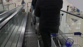 Compradores que van abajo por la escalera móvil en la alameda de compras almacen de metraje de vídeo