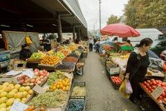 Compradores y comerciantes del mercado de la ciudad con los soportes de frutas y verduras frescas Fotografía de archivo libre de regalías