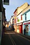 Comprando em uma rua estreita em Kinsale, cortiça do condado, Irlanda no 18 de março Lojas pequenas em uma cidade pequena Fotos de Stock