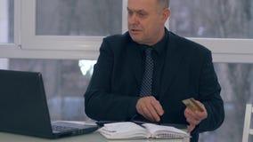 Comprando en línea, el pensionista con la tarjeta de crédito en una mano utiliza un ordenador portátil en oficina moderna almacen de video