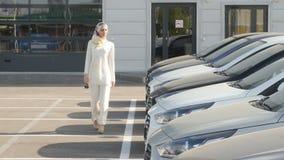 Comprando o alquilando un concepto del coche La mujer musulmán joven elige un coche para comprar o para alquilar almacen de metraje de vídeo