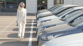 Comprando o alquilando un concepto del coche La mujer musulmán joven elige un coche para comprar o para alquilar almacen de video