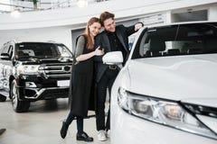 Comprando su primer coche junto Opinión de alto ángulo el vendedor de coches joven que se coloca en la representación que habla d imágenes de archivo libres de regalías