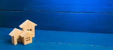 Comprando y vendiendo de las propiedades inmobiliarias, construcci?n Tres casas en un fondo azul Apartamentos y apartamentos Ciud fotografía de archivo libre de regalías