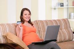 Comprar em linha da mulher gravida Imagens de Stock