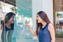 Compras adolescentes Biracial de la ventana de la muchacha en el ambiente urbano céntrico Imágenes de archivo libres de regalías