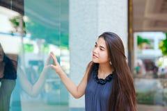 Compras adolescentes Biracial de la ventana de la muchacha en el ambiente urbano céntrico Foto de archivo libre de regalías