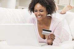 Compras afroamericanas del ordenador portátil de la muchacha en línea Foto de archivo libre de regalías
