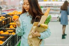 Compras asiáticas jovenes de la muchacha en un supermercado La mujer compra fruta y el producto lácteo imagenes de archivo