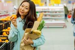 Compras asiáticas jovenes de la muchacha en un supermercado La mujer compra fruta y el producto lácteo fotografía de archivo libre de regalías