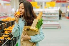 Compras asiáticas jovenes de la muchacha en un supermercado La mujer compra fruta y el producto lácteo imagen de archivo libre de regalías