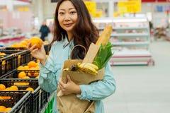 Compras asiáticas jovenes de la muchacha en un supermercado La mujer compra fruta y el producto lácteo fotos de archivo libres de regalías