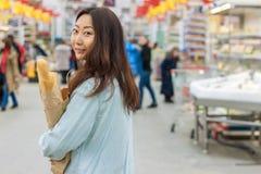 Compras asiáticas jovenes de la muchacha en un supermercado La mujer compra fruta y el producto lácteo imagen de archivo
