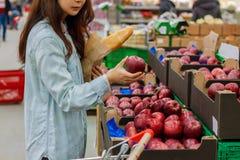 Compras asiáticas jovenes de la muchacha en un supermercado La mujer compra fruta y el producto lácteo imágenes de archivo libres de regalías