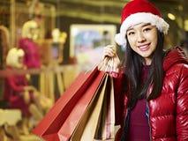 Compras asiáticas jovenes de la mujer para la Navidad imagen de archivo