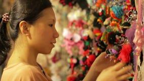 Compras chinas de la mujer joven en el mercado asiático de la noche almacen de metraje de vídeo