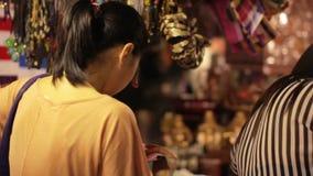 Compras chinas de la mujer joven en el mercado asiático de la noche almacen de video