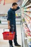 Compras confusas del hombre en el supermercado Imágenes de archivo libres de regalías