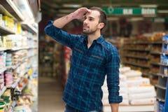 Compras confusas del hombre en el supermercado Imagen de archivo libre de regalías