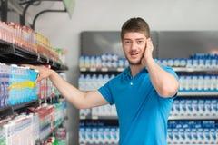 Compras confusas del hombre en el supermercado Imagen de archivo