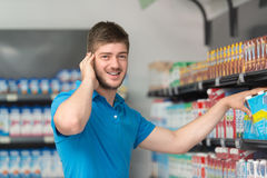 Compras confusas del hombre en el supermercado Foto de archivo libre de regalías