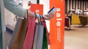 Compras de Internet, tarjeta de crédito en manos de mujeres con los bolsos de las compras de la porción de temporada de descuento almacen de metraje de vídeo