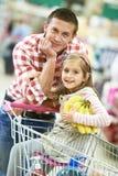 Compras de la familia en supermercado Fotos de archivo libres de regalías