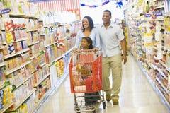 Compras de la familia en supermercado Imágenes de archivo libres de regalías