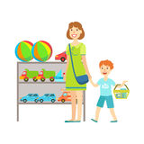 Compras de la madre y del niño para los juguetes, la alameda de compras y el ejemplo de la sección de los grandes almacenes Imágenes de archivo libres de regalías