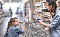 Compras de la madre y de la hija en el supermercado que elige productos fotografía de archivo libre de regalías