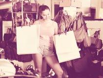 Compras de la muchacha del adolescente en tienda con los bolsos Foto de archivo