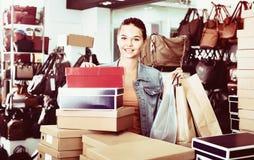 Compras de la muchacha del adolescente en tienda con los bolsos Foto de archivo libre de regalías