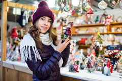 Compras de la muchacha en la feria festiva antes de Navidad Foto de archivo libre de regalías