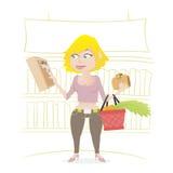 Compras de la muchacha en un supermercado foto de archivo