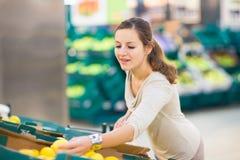 Compras de la mujer bonita, joven para las frutas y verduras en produc Imagen de archivo libre de regalías