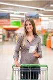 Compras de la mujer con la lista de comprobación y la carretilla Fotografía de archivo