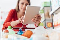 Compras de la mujer con su tableta fotografía de archivo