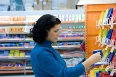 Compras de la mujer en el supermercado Foto de archivo libre de regalías