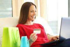 Compras de la mujer en línea con la tarjeta de crédito Imágenes de archivo libres de regalías