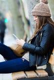 Compras de la mujer en la ciudad con su smartphone Foto de archivo libre de regalías