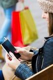 Compras de la mujer en la ciudad con su smartphone Fotos de archivo