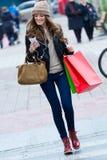 Compras de la mujer en la ciudad con su smartphone Fotos de archivo libres de regalías