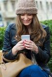 Compras de la mujer en la ciudad con su smartphone Imagenes de archivo