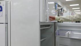 Compras de la mujer en la tienda de Sears para vender el refrigerador almacen de metraje de vídeo