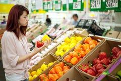 Compras de la mujer en supermercado Fotografía de archivo libre de regalías
