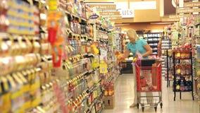 Compras de la mujer en supermercado almacen de video